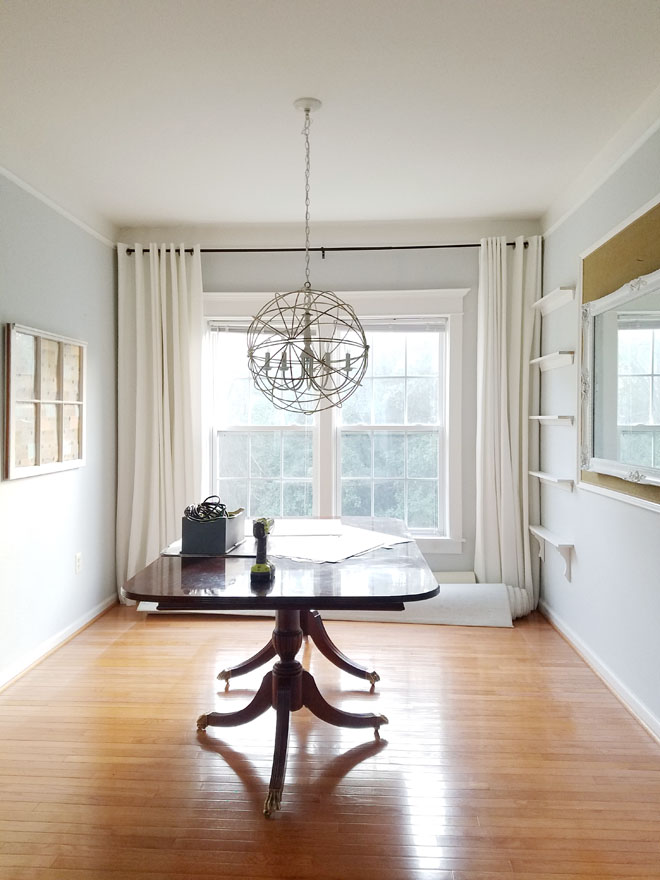 classic table in dining room with white drapes and oak floors