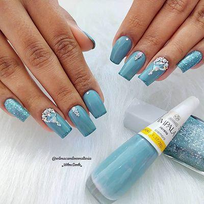 unhas decoradas com esmalte azul e pedrinhas