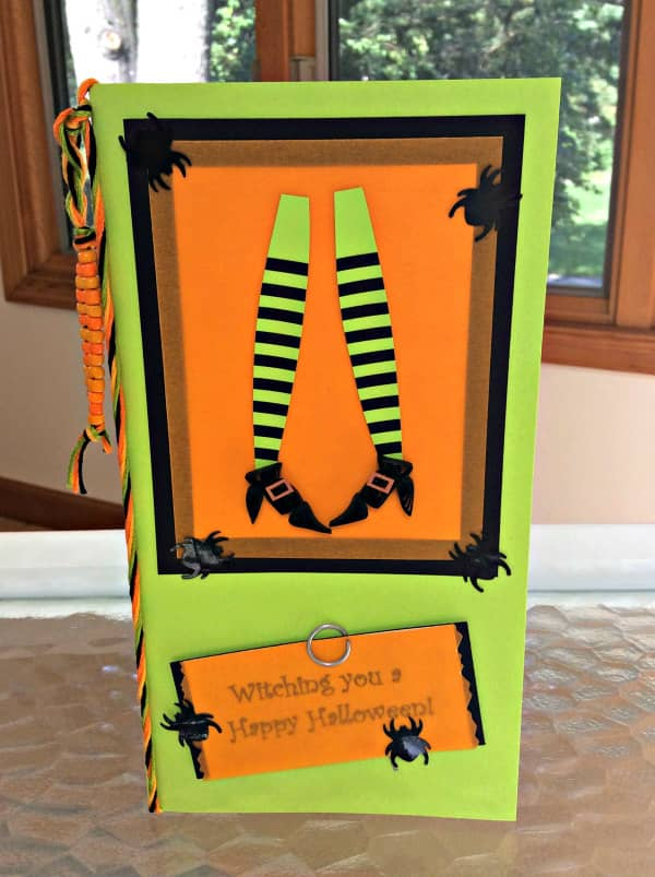 handmade Halloween card with witch legs wearing striped stockings and quilled black booties