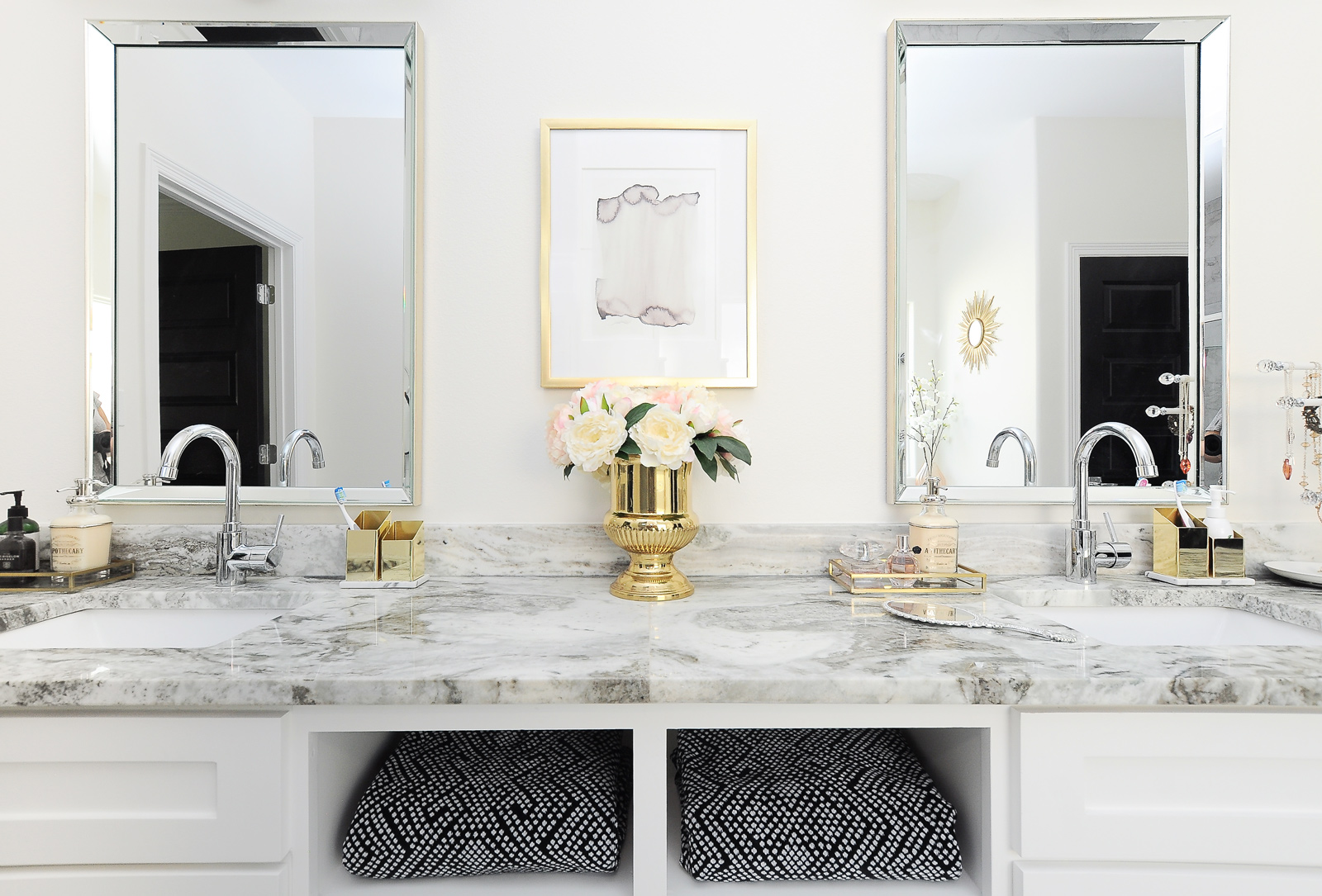Bright white and gold master bathroom with marble look granite counters and chrome fixtures.