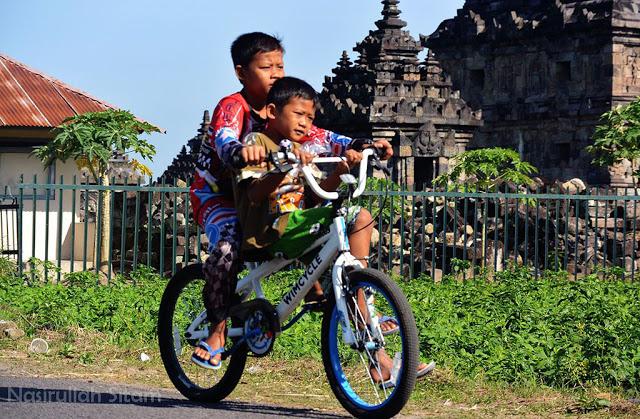 Dua anak sedang menikmati akhir pekan menaiki sepeda