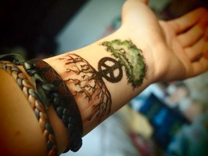 tatuaje en la muñeca de una chica, es el tatuaje de un arbol con raices y el simbolo de la paz