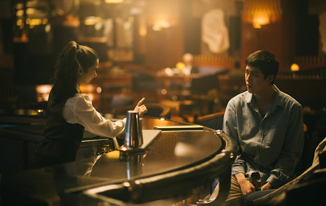 A female bartender serves a drink to a boy at a bar
