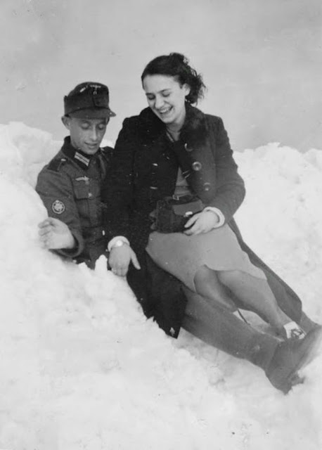 A friendly visit with a Wehrmacht Gebirgsjager (mountain) Troops private in a snowdrift. She appears to have nylons on, he apparently was quite thoughtful to get them for her - nylons were absolutely cutting edge style in the '40s.