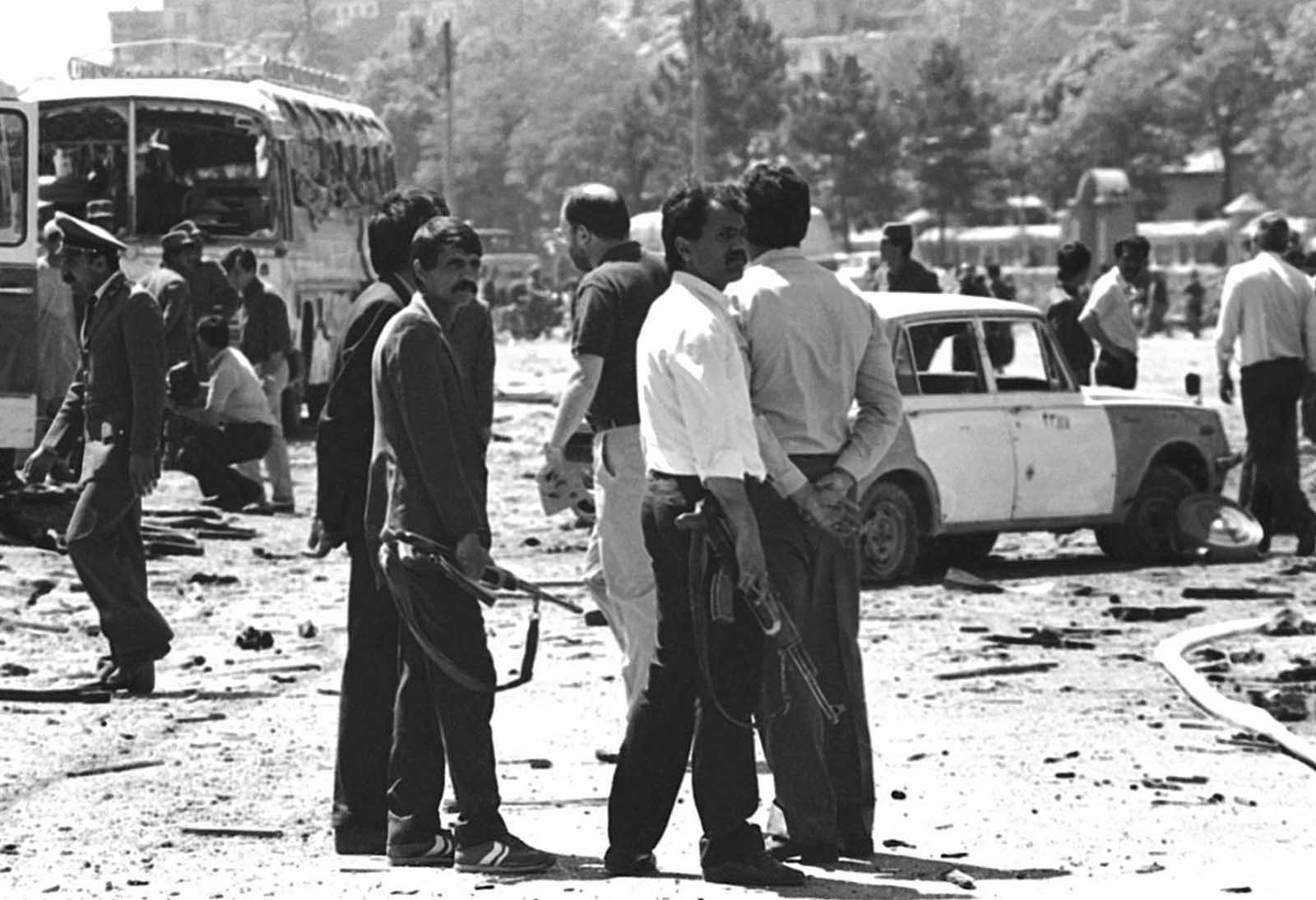 Police and armed Afghan militiamen walk amid the debris after a bomb, allegedly placed by the Mujahideen rebels, exploded in downtown Kabul during celebrations marking the 10th anniversary of the Afghan revolution backed by the Soviet Union on April 27, 1988.
