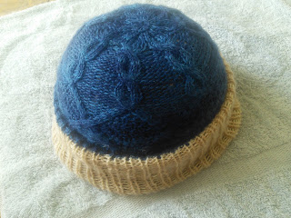 A cabled hat knit in worsted-weight yarn.  The hat is blue, and the turned up ribbed brim is an off-white.  The hat is drying over a bowl, and resting on a towel.