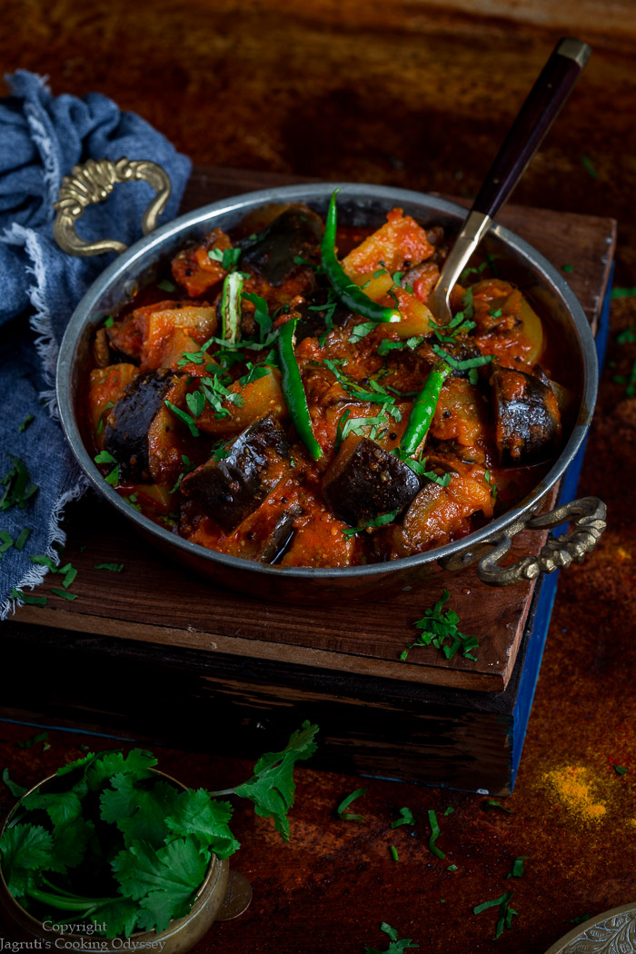 Ringana bateta nu saak served in a small copper kadai garnished with cilantro and green chillies .