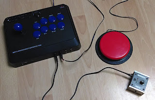 Image of a black and blue arcade stick adapted for switch use, pictured with a red able net switch and a Shout Box.
