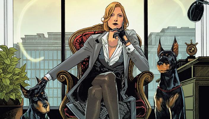 Imagem: a vilã Veronica Cale dos quadrinhos, uma mulher branca e loira num terno cinza numa poltrona de escritório e ao seu lado seus cachorros, três dobbermans.