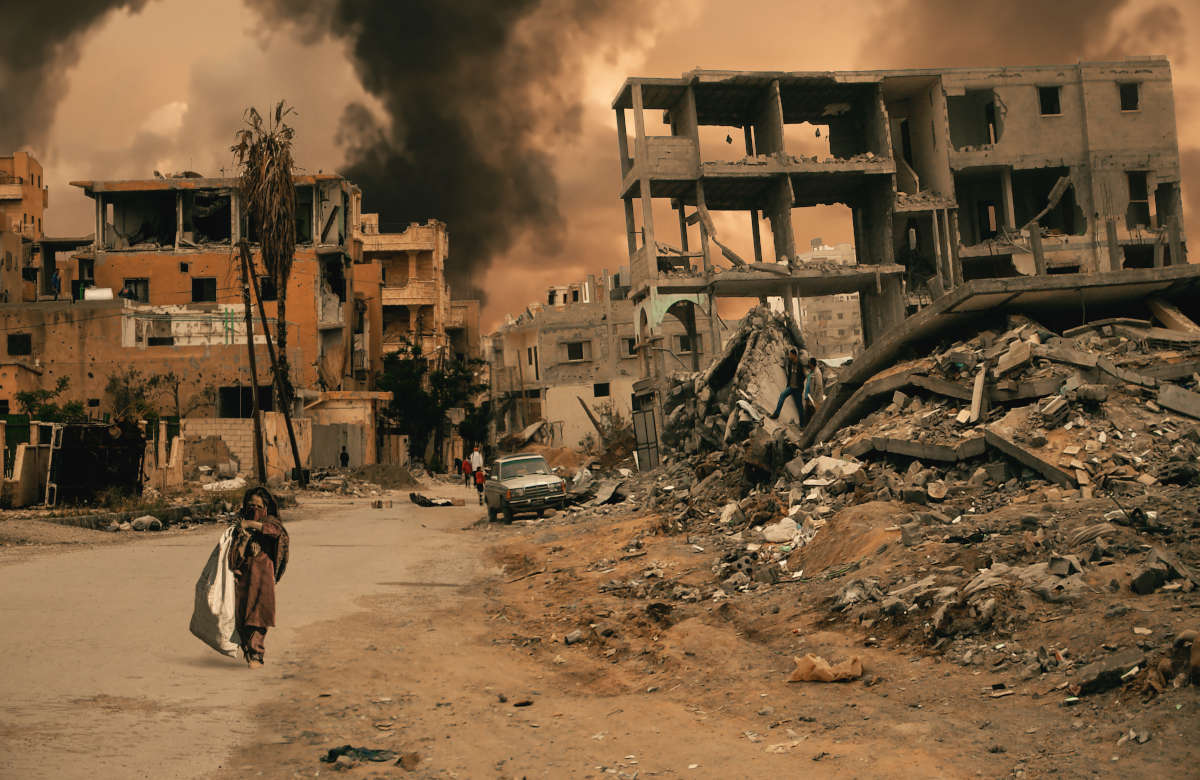 A war-torn city with a child sitting in front