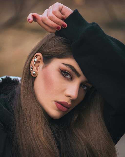 Brunette woman with multiple ear piercings.