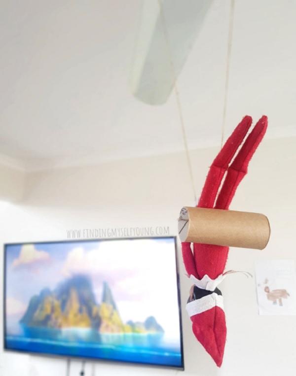 elf on the shelf hanging upside down on swing