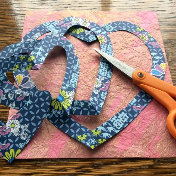 paper cut heart shapes with scissors and gilded paper