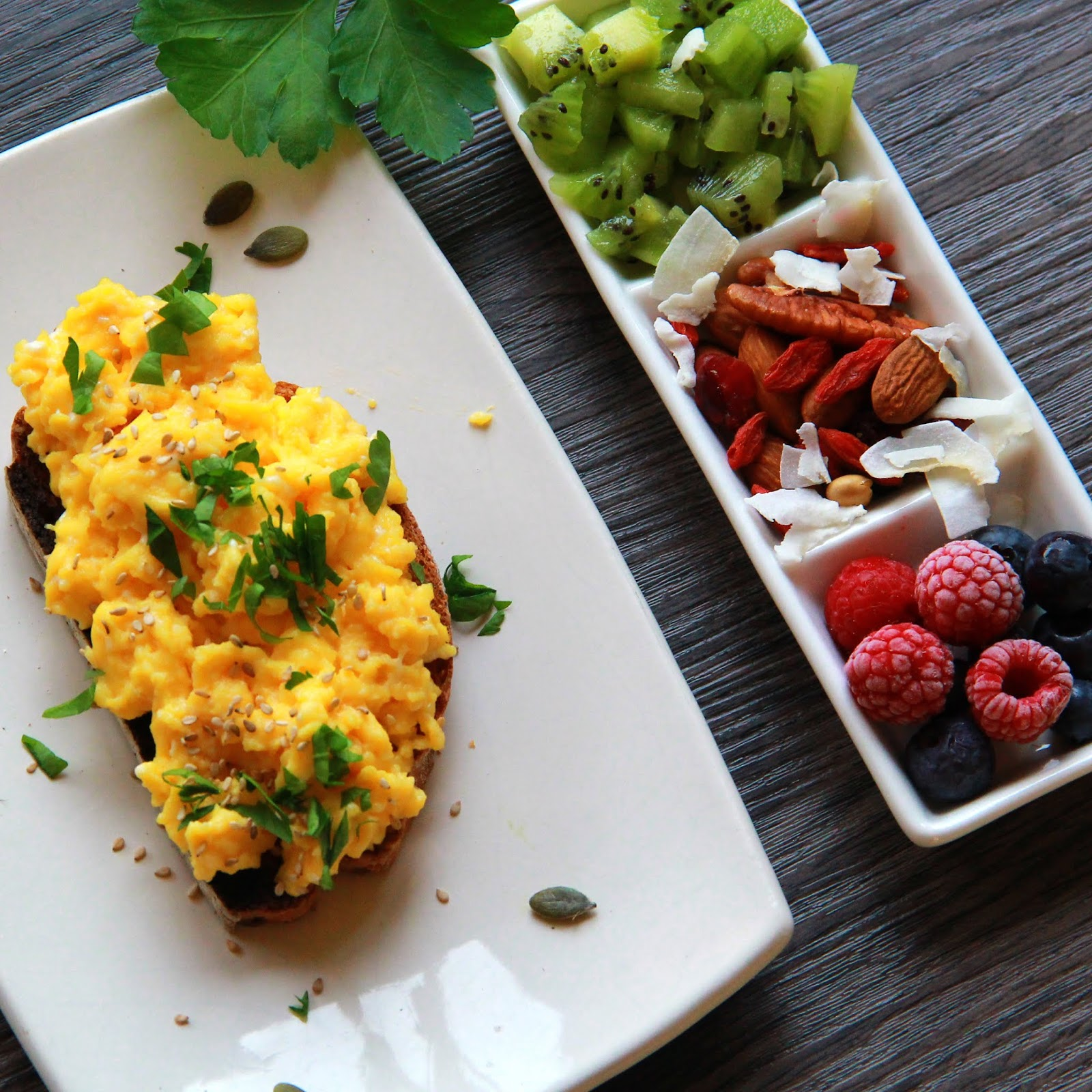 Toast de pain complet aux œufs brouillés, kiwi, fruits rouges et noix