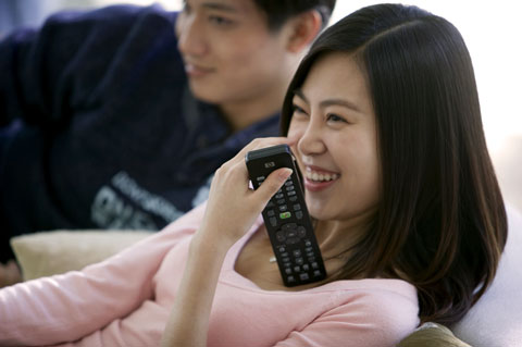 Young Beijing couple watching TV, woman holding remote control