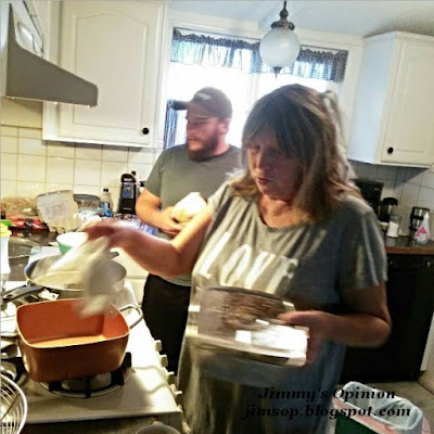 My wife Cindy and son Tim cooking bacon and eggs in front of the stove