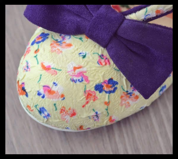 close up of toe of shoe with purple floral bow