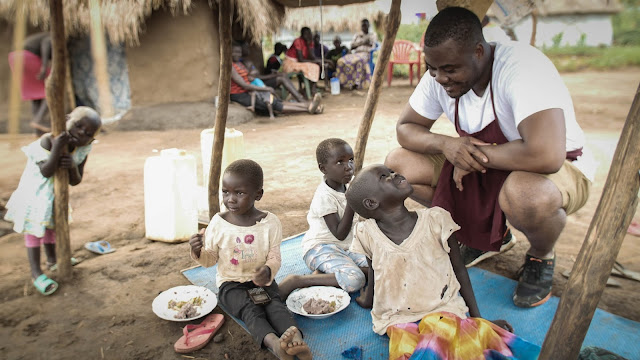 Selasi meets refugee children for share a meal in Uganda