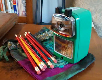 Sharpened pencils arranged next to a 'Groovy Green' pencil sharpener from Classroom Friendly Supplies atop a blue, green and purple drawstring pouch on wooden table surface
