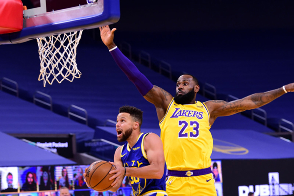 LeBron James tries to block a shot by Steph Curry in a game between the Los Angeles Lakers and the Golden State Warriors.