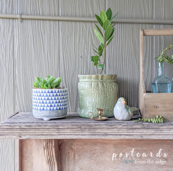 rustic outdoor mantel with blue and white planter and green stoneware bird