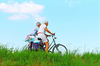 An elderly couple ride bicycles together