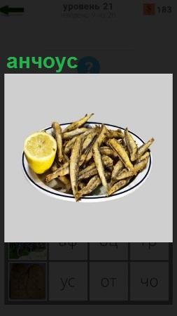 В тарелке лежит рыба анчоус с лимоном, приготовленная для еды