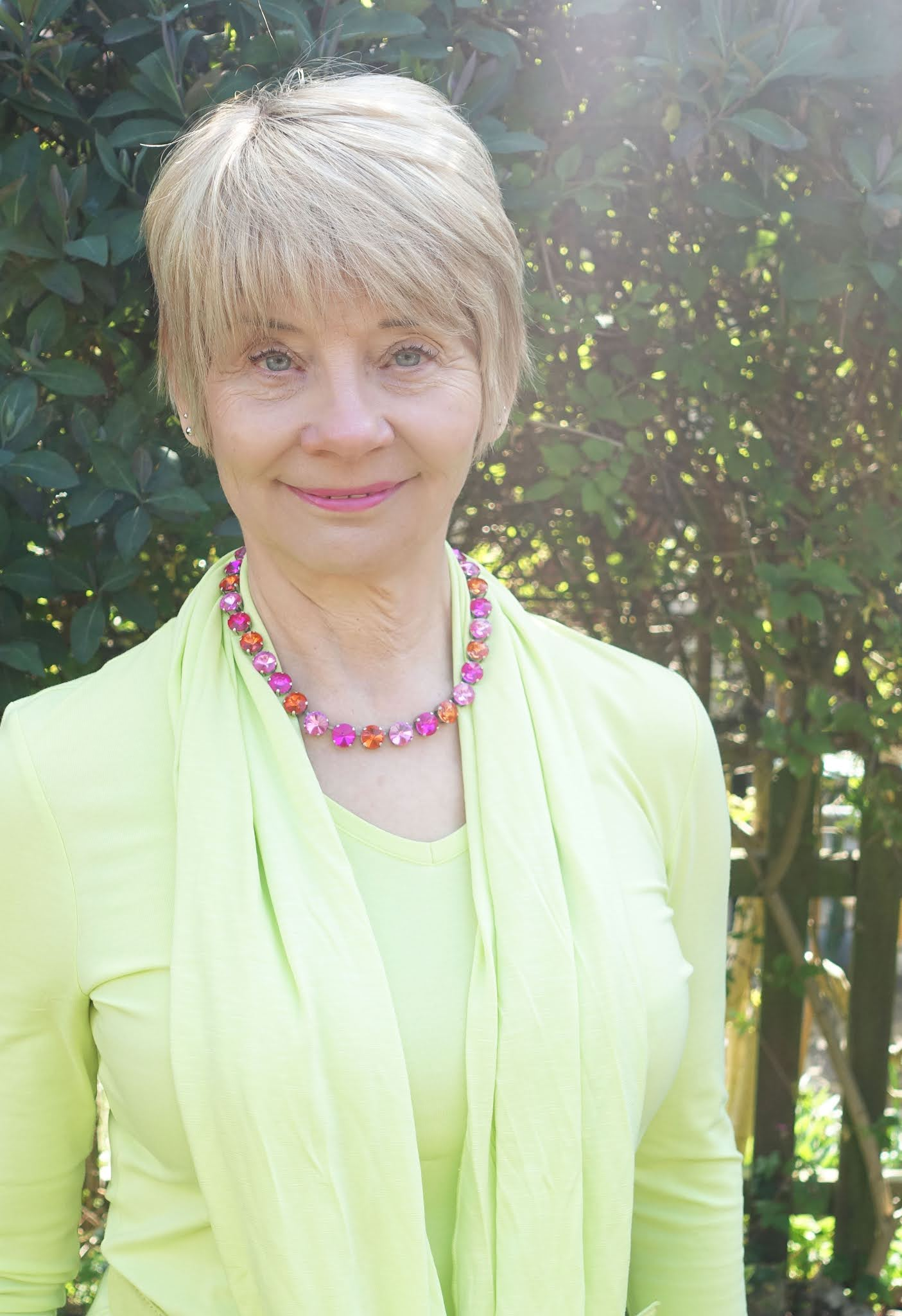 Head and shoulders shot of over-50s blogger Gail Hanlon in acid yellow with a pink crystal necklace