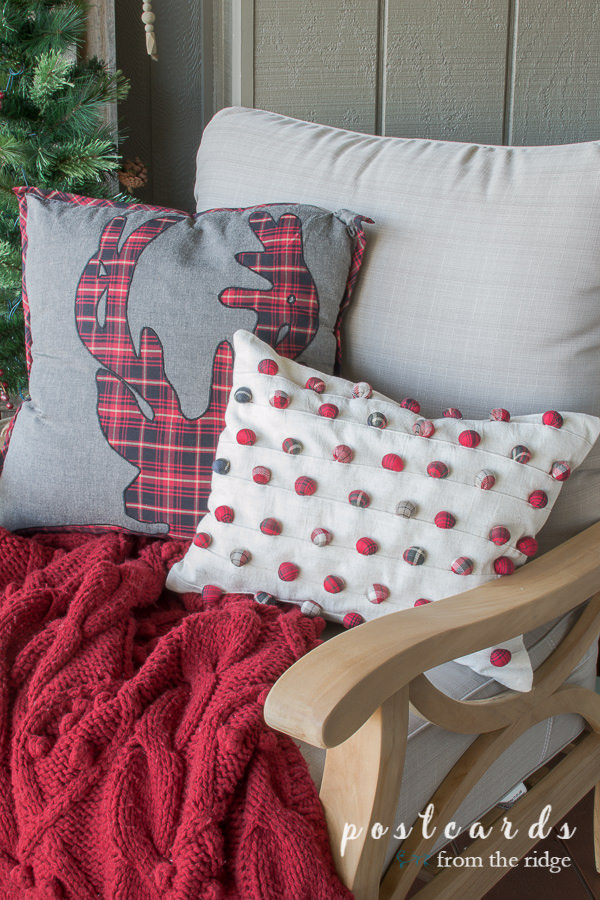 outdoor teak chair with red throw blanket and holiday pillows