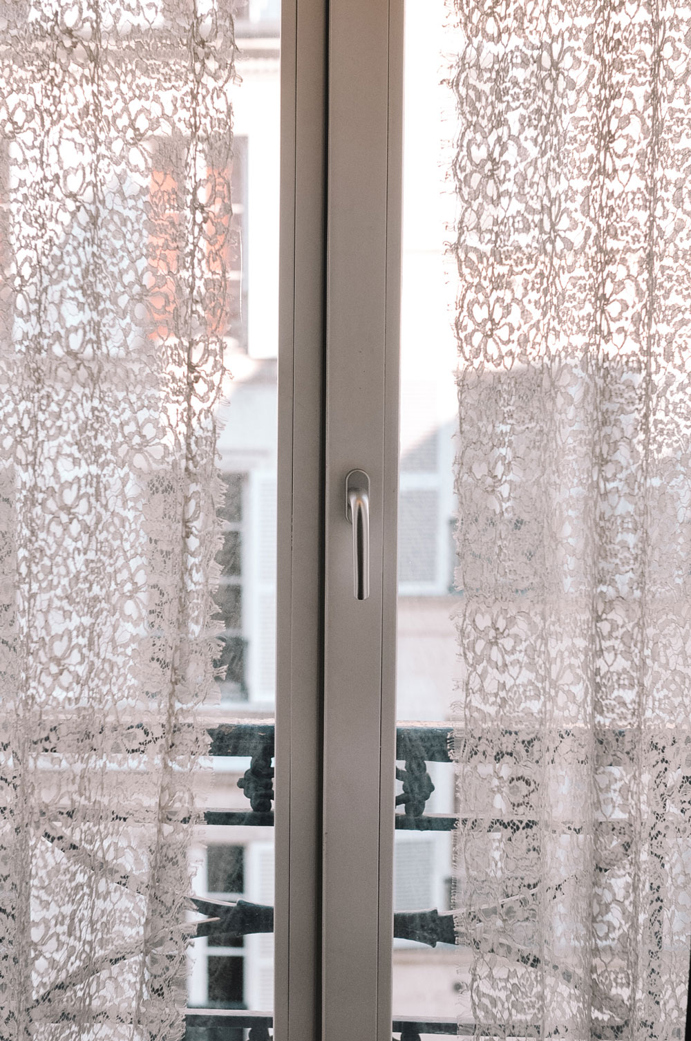 Lace curtains frame the beautiful view at Hotel Chavanel