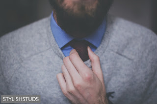 A men adjusting his tie which is under a V-neck sweater.