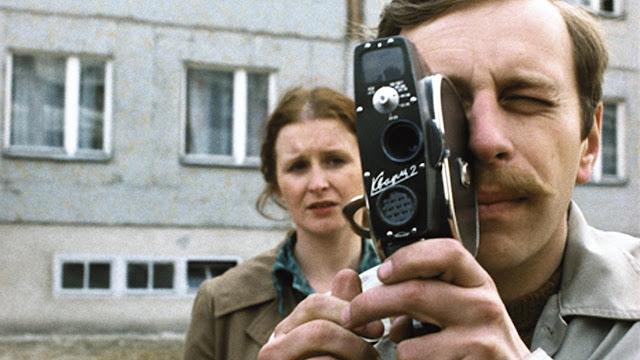 Filip capturing the mundane happenings in the neighborhood as his exasperated wife Irka stands behind