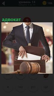 В зале заседаний адвокат собирает в портфель свои документы