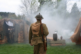 Reenactor portraying World War I soldier beside trench set-up