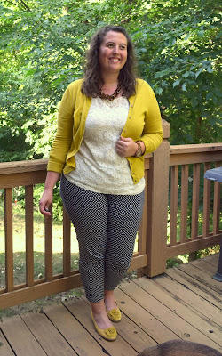 an outfit with a white lace shirt, a mustard cardigan, a tortoiseshell necklace, navy pants, and mustard flats