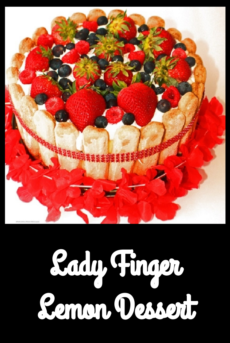 this is a no bake dessert made with lady fingers, lemon pudding, whipped cream and topped with fresh strawberries, blueberry, raspberries using a springform pan tied with a red ribbon