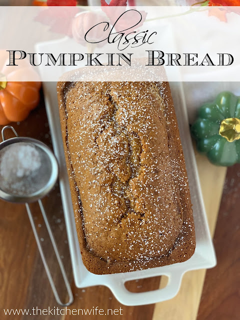 The finished pumpkin bread loaf on a white platter with fall decor around it and the title above.