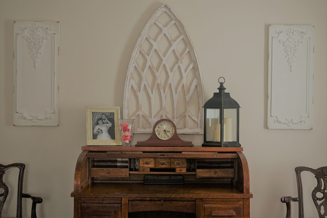 Clock and lantern styled on top of roll top desk