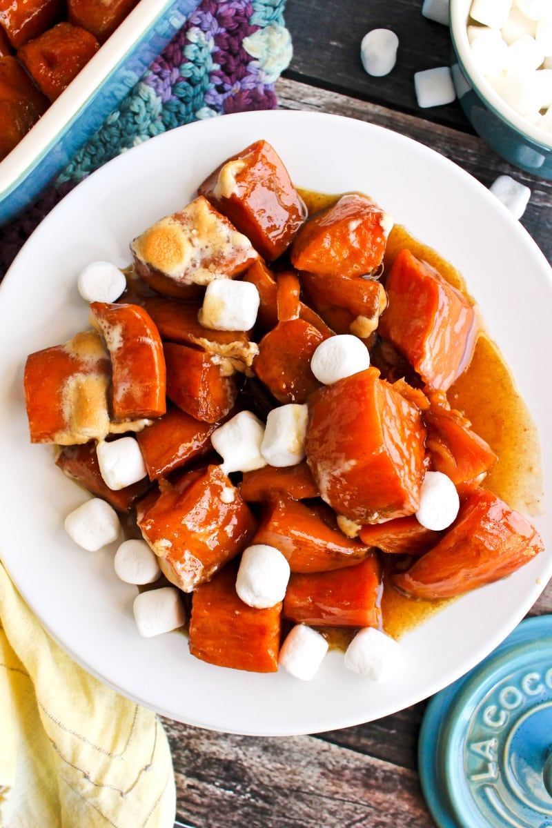 Top view of Candied Sweet Potatoes with Marshmallows on a white plate on a rustic wood background.