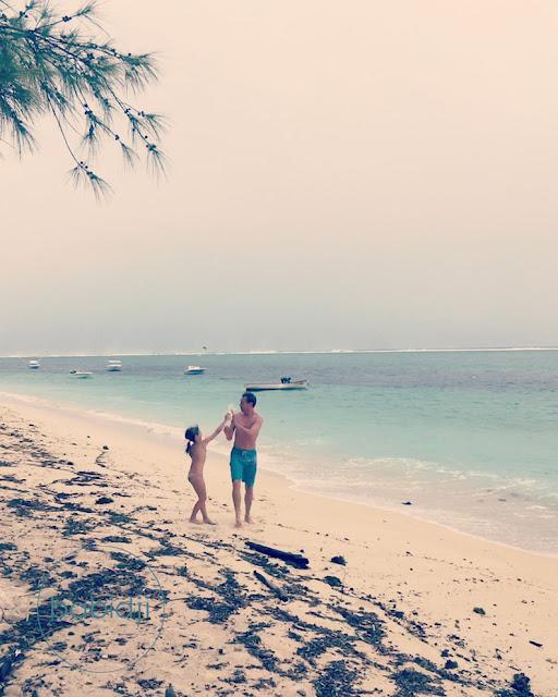 fille qui arrose son père pour jouer sur la plage du Morne à l'Île Maurice