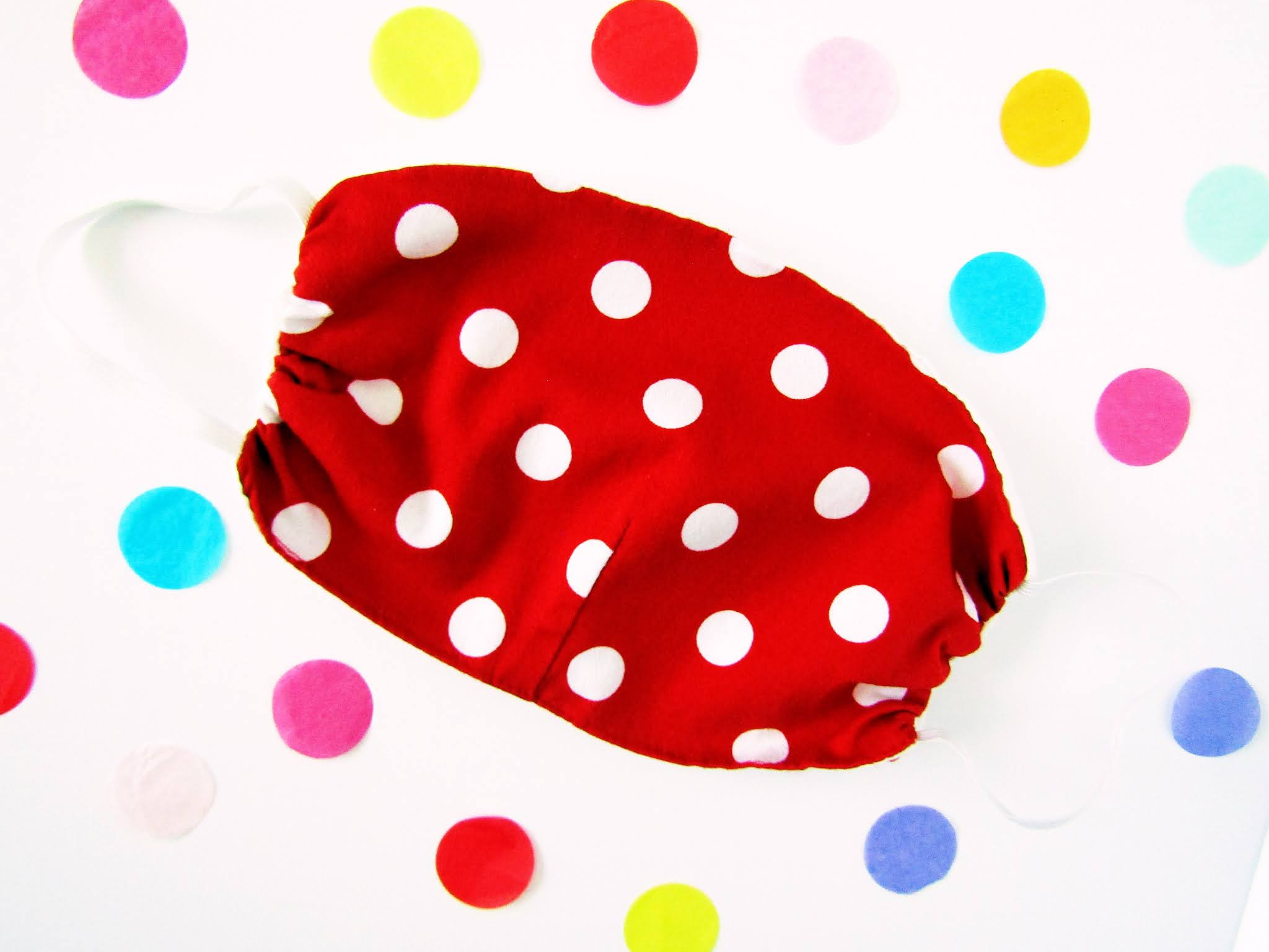 A flatlay photo of a red and white polka dot face covering from Lady Vintage, on a white background surrounded by colourful round confetti.