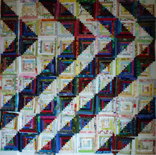 Multicolored scraps cut into half-inch logs make this quilt.