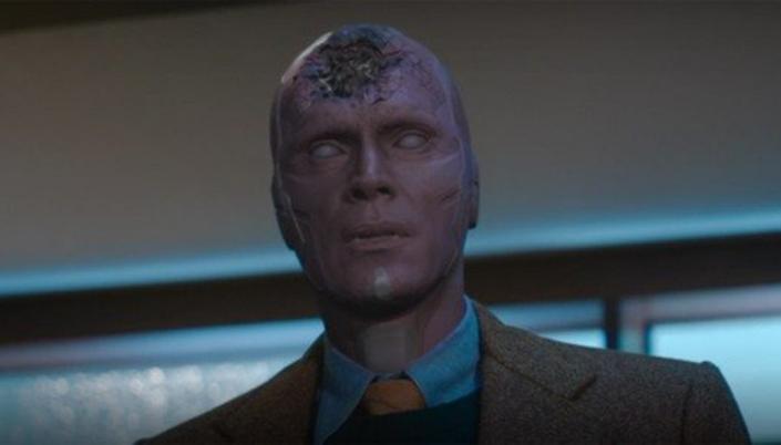 Imagem: cena com o Visão morto, a pele vermelha sintética sem cor, os olhos apagados e brancos, a testa destruída sem a sua pedra do infinito amarela, mas ele está em um terno guarda-pó e em pé.