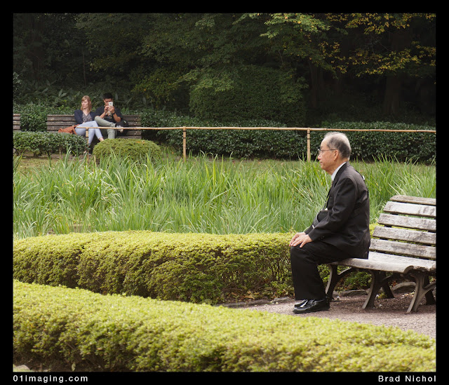 Man sitting upright on chair in east garden imperial palace grounds Tokyo Japan.
