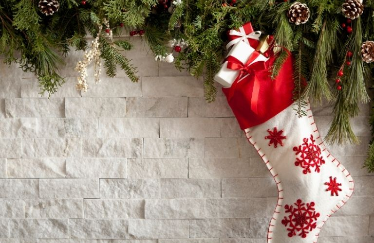 Red and white Christmas stocking on white break background with evergreen leaves