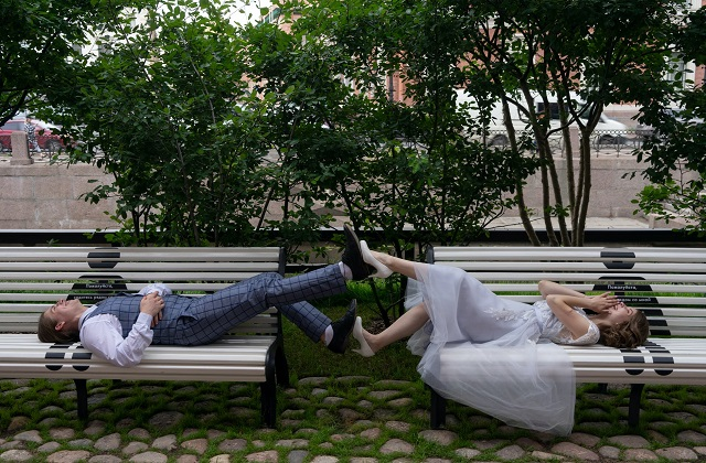 married couple lying on bench playing feet