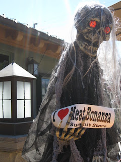 "Ghoul with glowing red eyes, holding a sign ""I (heart) Meat Bonanza, Summit Store,"" Los Gatos, California"