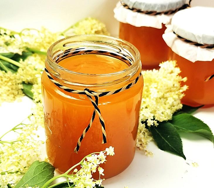 Holunderblütengelee mit Mandarinensaft im Glas und Holunderblüten