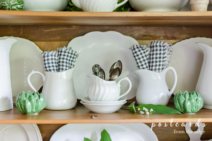 black and white napkins and white stoneware in a vintage oak hutch