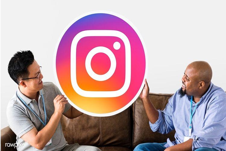 Duas pessoas segurando o logo do Instagram